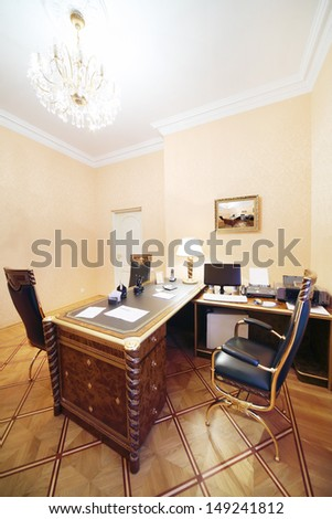 Workplace with computer and soft armchair in home office in classic style. - stock photo