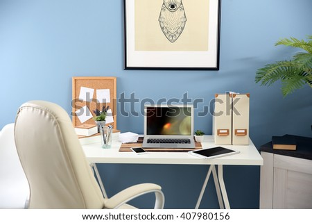 Workplace with different devices, stationery and table on blue wall background - stock photo