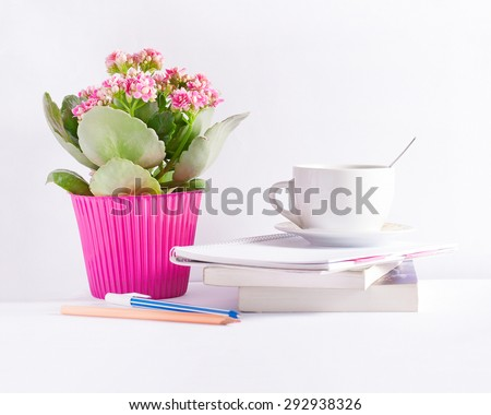 Workplace with flower books and a coffee cup with