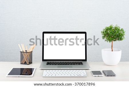Workplace with modern gadgets. Laptop on a table with blank screen