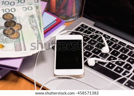 Workplace with money and electronic devices - cellphone, headphones for music and laptop computer. Mobile phone and Polish money banknotes on keyboard of notebook. Concept of payment and savings. - stock photo