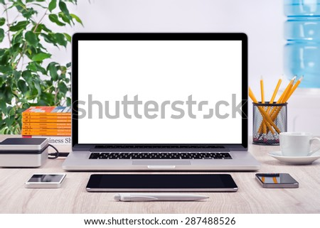 Workplace with open laptop mockup different gadgets and office supplies on the desk. For design presentation or portfolio. All devices in focus. - stock photo