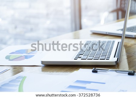 Workplace with open laptop with analysis chart and modern wooden desk, angled notebook on table in home interior, filtered image, selective focus. - stock photo