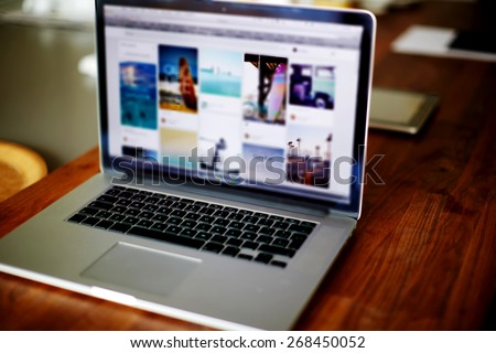 Workplace with open laptop with black screen on modern wooden desk, angled notebook on table in home interior, filtered image, cross process - stock photo