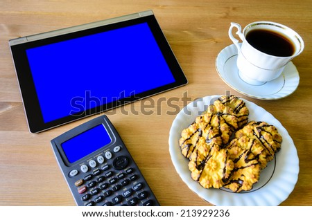 workplace with tablet pc - blue box, calculator, cup of coffee and cookies - stock photo - stock photo