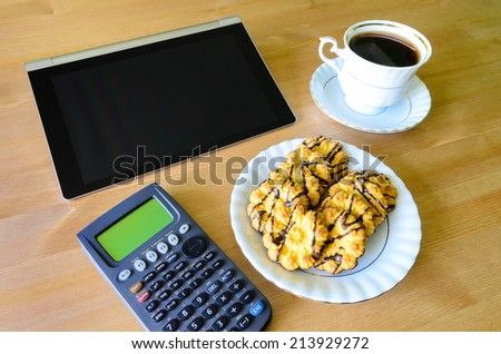 workplace with tablet pc, calculator, cup of coffee and cookies - stock photo - stock photo