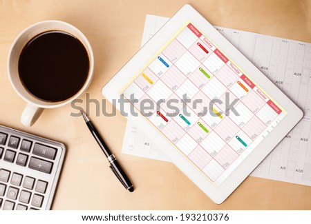 Workplace with tablet pc showing calendar and a cup of coffee on a wooden work table close-up - stock photo