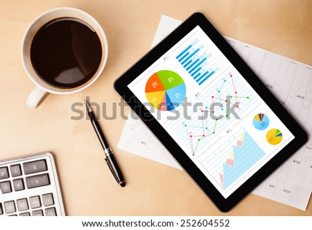 Workplace with tablet pc showing charts and a cup of coffee on a wooden work table close-up - stock photo