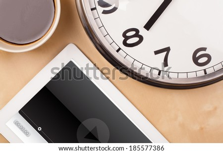 Workplace with tablet pc showing media player and a cup of coffee on a wooden work table close-up - stock photo