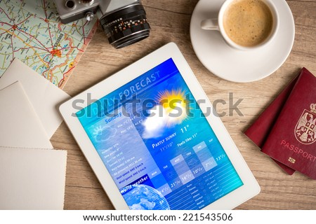 Workplace with tablet pc showing weather forecast and a cup of coffee on a wooden work table  - stock photo
