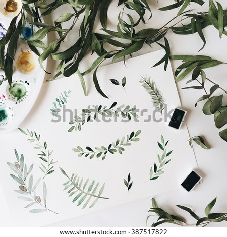 Workspace. Green leaves painted with watercolor isolated on white background. Overhead view. Flat lay, top view - stock photo
