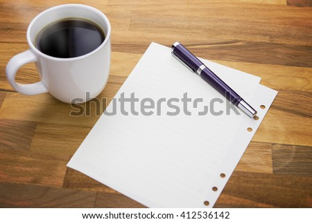 Workspace with hot coffee cup, note paper and pen on wooden table