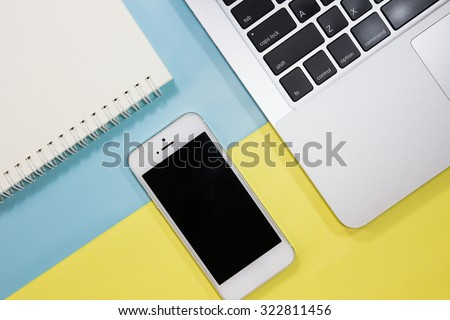 Workspace with laptop, sketchbook and mobile on pastel background,Work space for designer or hipster style. - stock photo