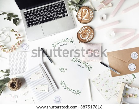 Workspace. Workspace with laptop, handmade invitation lists, craft envelope, pen, twine, candles and watercolor paintings on white background. Overhead view. Flat lay, top view - stock photo
