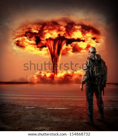 World Apocalypse. Man in gas looking on big red mushroom of Nuclear explosion outdoor. environmental protection concept and the dangers of nuclear energy.  - stock photo