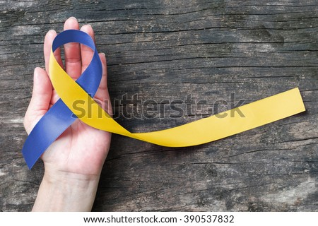World down syndrome day WDSD March 21: Blue yellow color fabric ribbon on human hand old aged background: Symbolic logo concept to support children & adult live with mental illness - stock photo