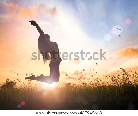 World environment day concept: Silhouette of happy woman jumping with her hands raised at orange nature sunset background