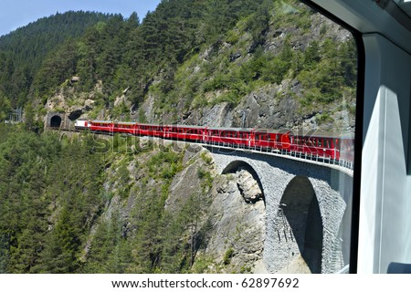 world famous swiss train Glacier Express makes it's way over a high viaduct into a tunnel, seen from inside the train - stock photo