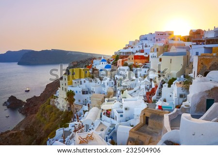 World famous traditional whitewashed chuches and houses of Oia village on Santorini island, Greece. Sunset. - stock photo