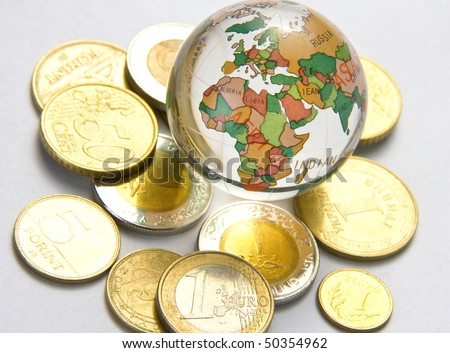 World globe and different coins - stock photo