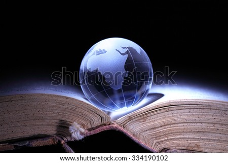 World Literature Concept. Glass globe on old book on dark background - stock photo