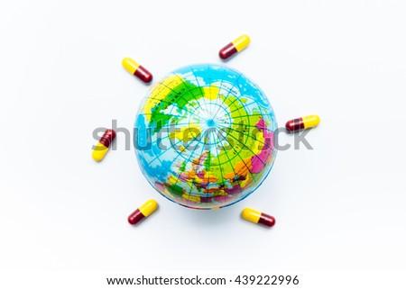 World map and medicine capsules (The world needs healing) - stock photo
