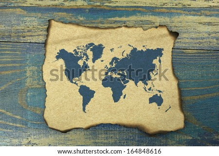 world map on burnt paper on blue old wood background - stock photo