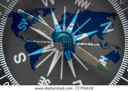 world map on glass compass - stock photo