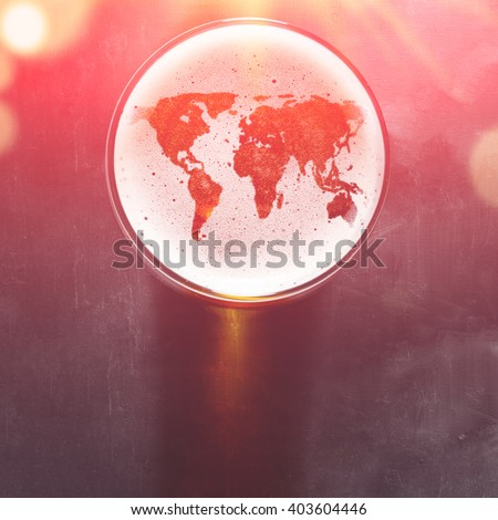 world map silhouette on foam in beer glass on black table. The continents shapes are altered ones from visibleearth.nasa.gov - stock photo