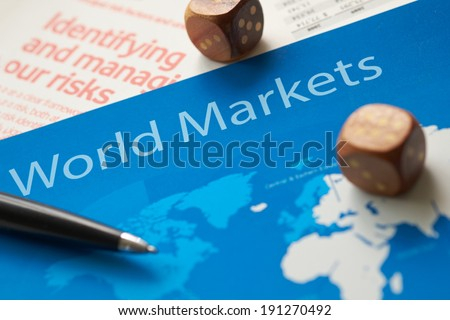 World markets documents with dice and pen.