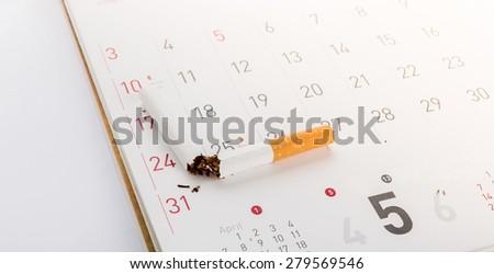 World No Tobacco Day : Broken cigarette on calendar ,sun flare filter effect - stock photo