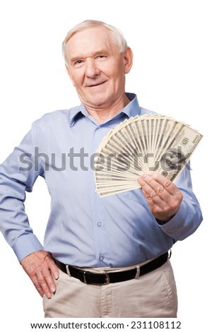 World of rich men. Portrait of senior man smiling at camera and holding money in his hands while standing against white background  - stock photo