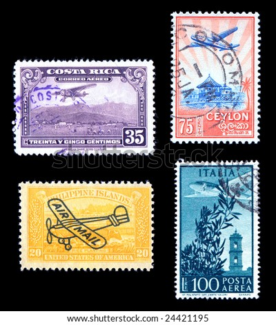 World postage stamps with airplanes cancelled isolated on black - stock photo