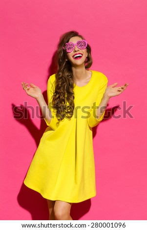 World Through Pink Sunglasses. Beautiful young woman in yellow mini dress and pink heart shaped sunglasses posing with arms outstretched. Three quarter length studio shot on pink background. - stock photo