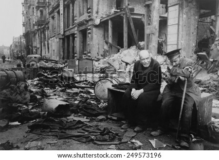 World War 2, Battle of Berlin, May 1945. Two elderly German men, one wearing the armband signifying blindness, the other his helper, sitting on a crate amid the rubble. Photo by Yevgeny Khaldei. - stock photo