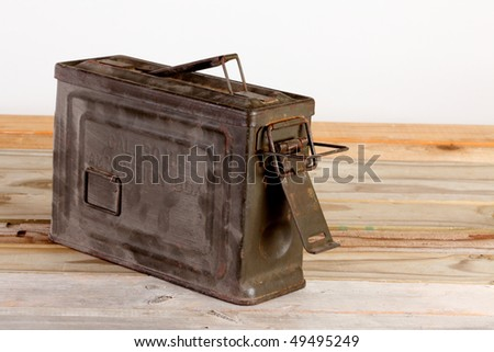 World War Two metal container for thirty caliber ammunition on a weathered wooden plank deck against white background - stock photo