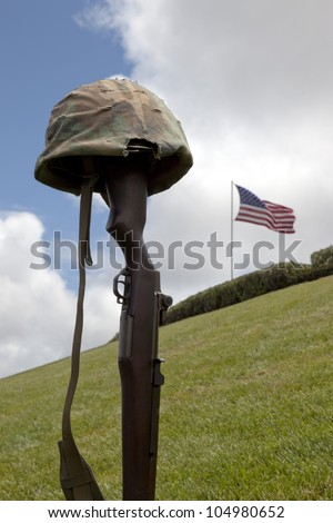 World War Two vintage Garand rifle and soldier's helmet forming Fallen Soldier Battle Cross, American Flag behind. - stock photo
