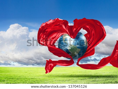 World within the heart symbol on blue sky background.Elements of this image furnished by NASA. - stock photo