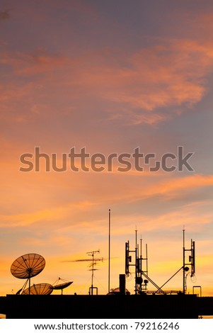 Worldwide Communication,  Satellite and other antenna network against beautiful sky at sunset - stock photo