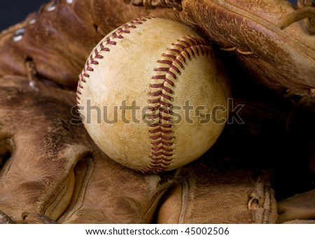 Worn baseball laying in an old glove - stock photo