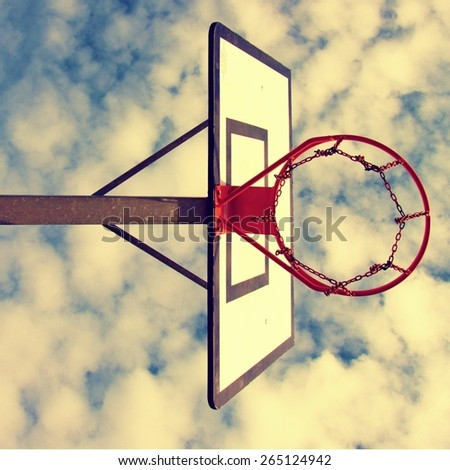 Worn basketball backboard with rusty hoop above street court. Blue cloudy sky in background.  - stock photo