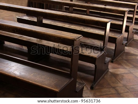 Worn Church pews in a basilica in Italy.