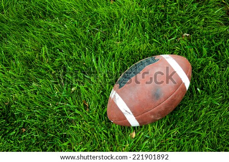 Worn Football on Grass. - stock photo