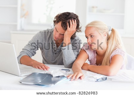 Worn out couple doing their accounting in their living room