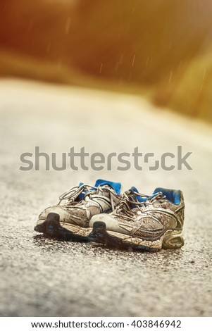 Worn-out mens running shoes standing on a desolate country road in a rainy day. Sports, active lifestyle, running, marathon, individual sports concept.