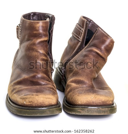 Worn out old boots isolated over white background - stock photo