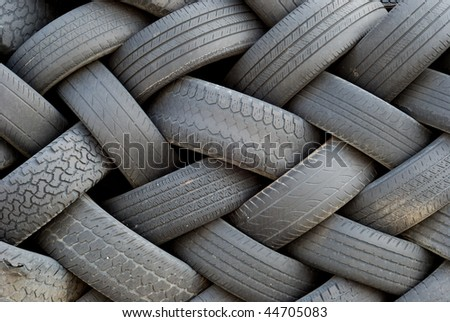 Worn out old tires, stacked artfully - stock photo