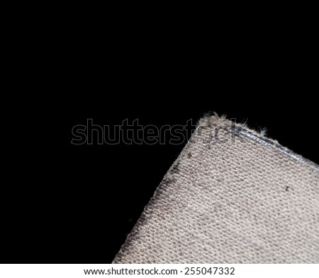 Worn textile cover of the old book isolated on black background