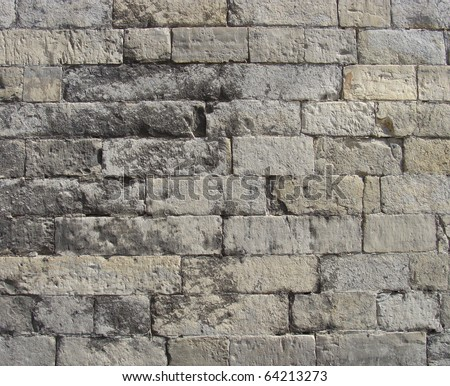 worn very old large stone wall in gray and beige - stock photo