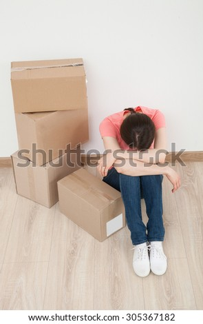 Worn young woman sitting on the floor near the pipe of boxes